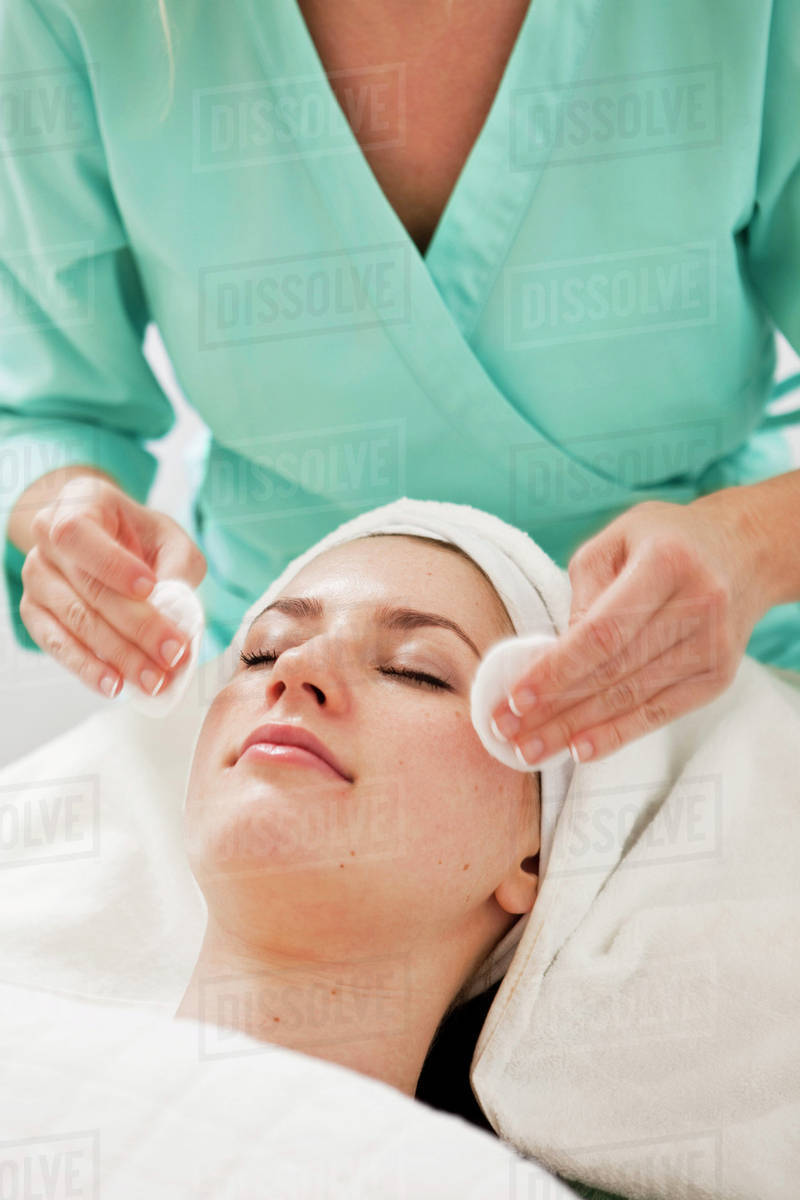 Midsection of a beautician cleaning young females face with bath ...