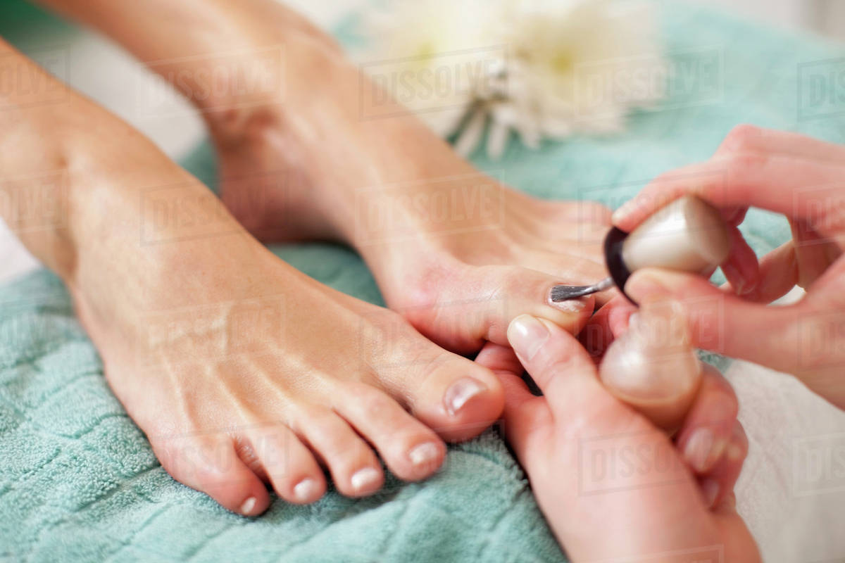 close-up of a female feet receiving a beauty treatment for nails in
