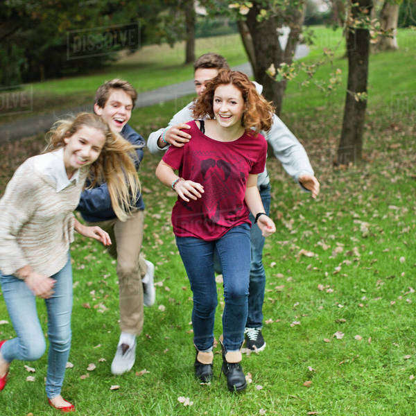 Playful boys chasing female friends at park Royalty-free stock photo