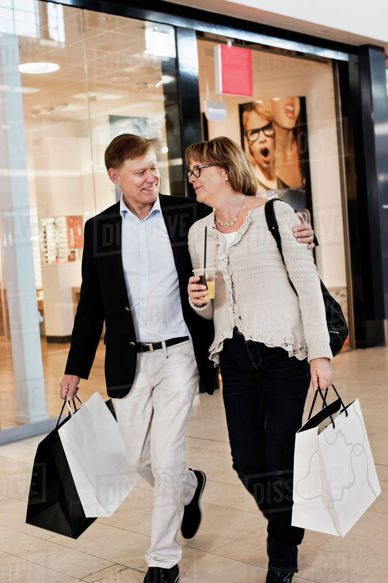 7652081e49 Happy senior couple with shopping bags walking by store in mall ...