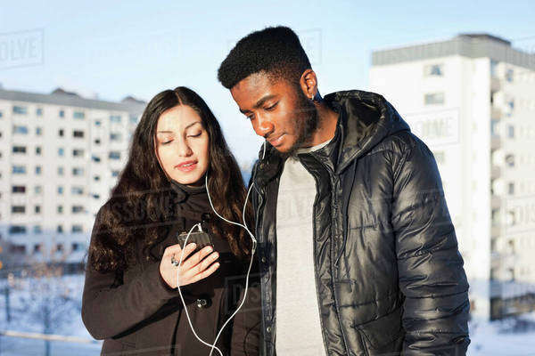 Young friends listening music through hands-free device against buildings Royalty-free stock photo