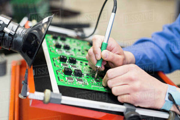 Cropped image of electrician's hand soldering circuit board Royalty-free stock photo