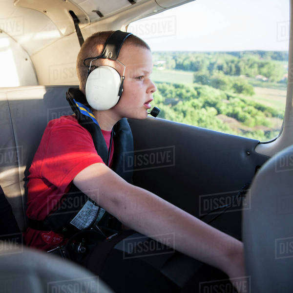 Boy looking through window of private plane Royalty-free stock photo