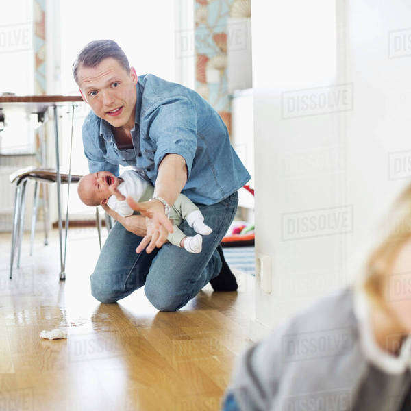 Father holding crying baby while stopping daughter on floor at home Royalty-free stock photo