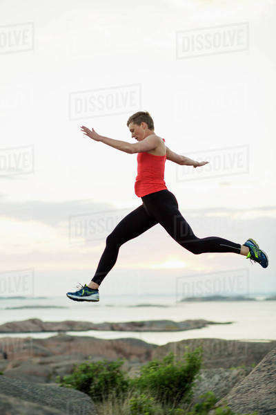 Side view of sporty woman crossing rocks at seaside Royalty-free stock photo