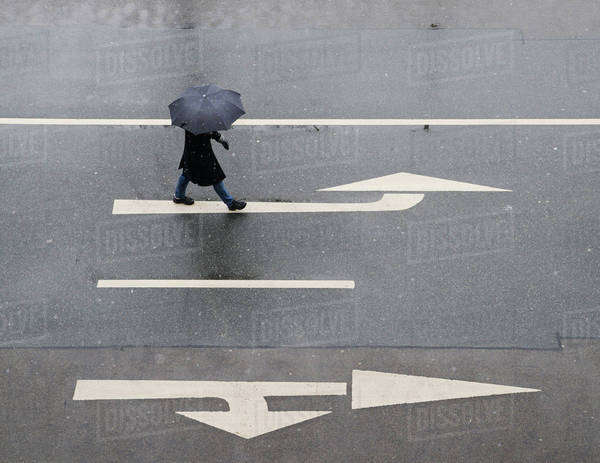 High angle view of woman with umbrella walking on road Royalty-free stock photo
