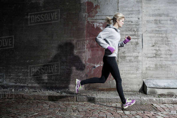 Full length of woman jogging on street Royalty-free stock photo