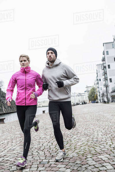Sporty couple running on street Royalty-free stock photo
