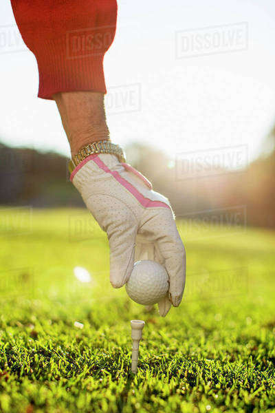 Woman placing golf ball on tee Royalty-free stock photo