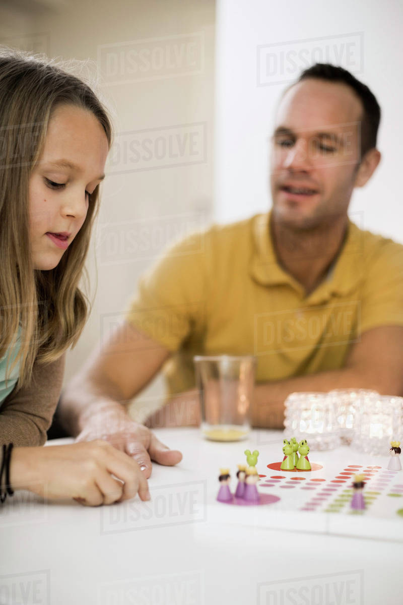 Father And Daughter Playing Ludo At Coffee Table