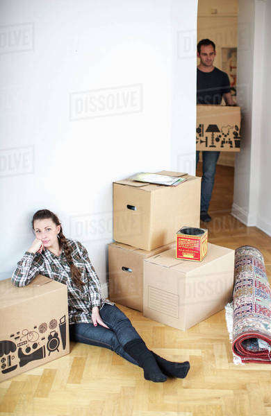 Full length of woman sitting on floor while man carrying cardboard box in new house Royalty-free stock photo