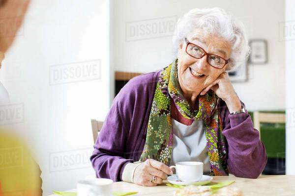 Happy senior woman looking at friend while having coffee at breakfast table in nursing home Royalty-free stock photo
