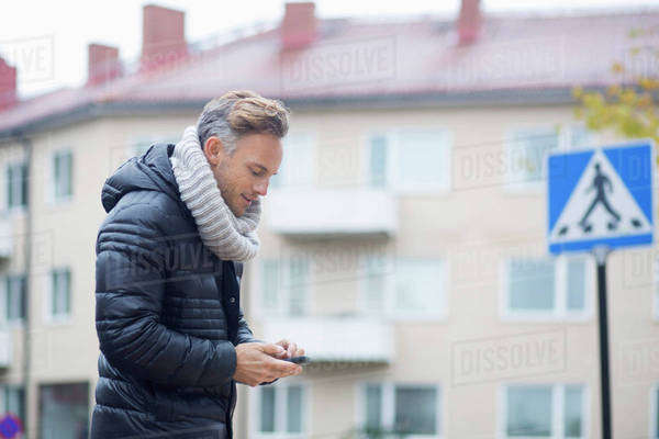 Mature man using smart phone against building Royalty-free stock photo
