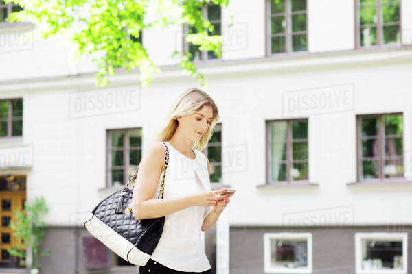Young woman using mobile phone while walking in city Royalty-free stock photo