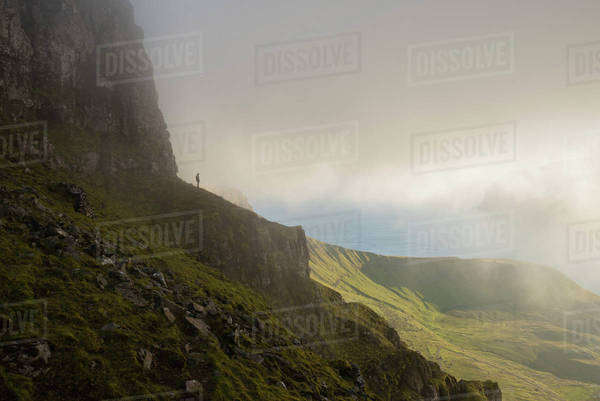 Distant view of man standing on cliff against cloudy sky Royalty-free stock photo