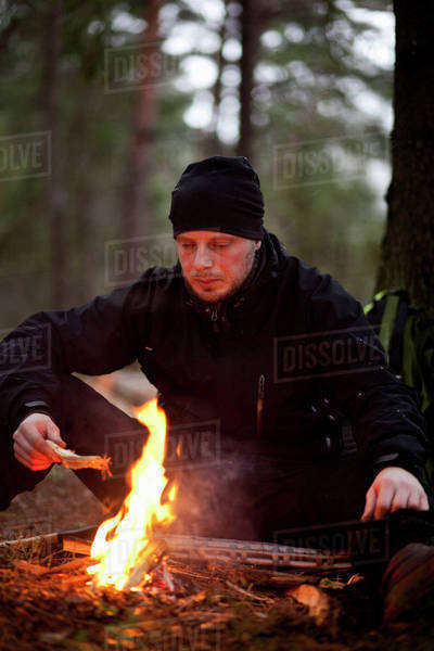 Man sitting by bonfire in forest Royalty-free stock photo