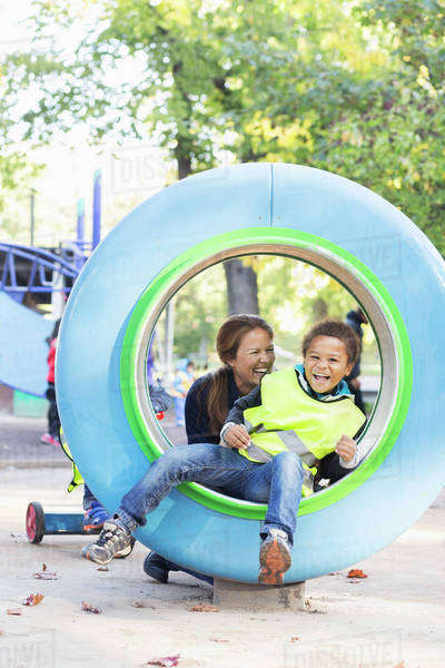 Happy teacher playing with boy in tube at playground Royalty-free stock photo