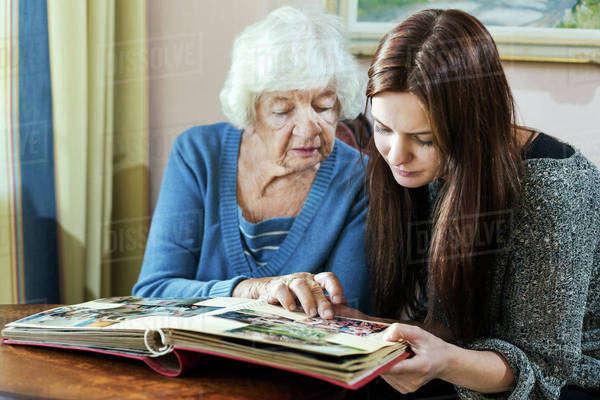 Grandmother and granddaughter looking at photo album in house Royalty-free stock photo
