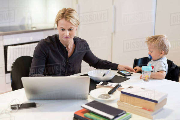 Woman working on laptop while taking care of son at dining table Royalty-free stock photo