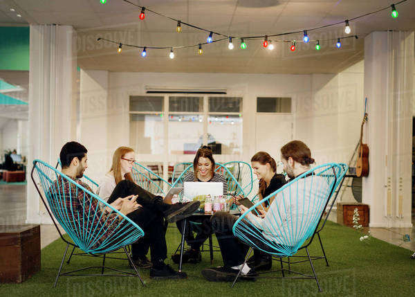 Creative business people using technologies in office canteen Royalty-free stock photo