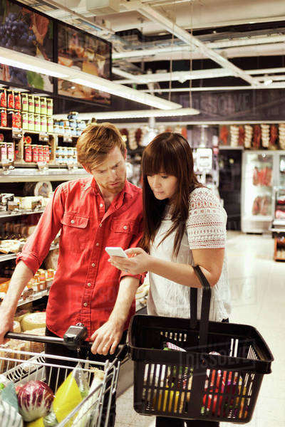 Couple using mobile phone at supermarket Royalty-free stock photo