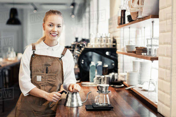 Portrait of happy female barista standing at counter in coffee shop Royalty-free stock photo