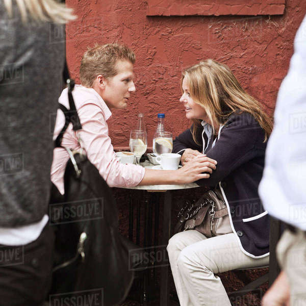 Mid adult couple at sidewalk cafe talking Royalty-free stock photo