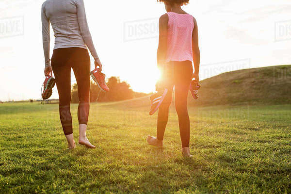 Low section of mother and daughter holding sports shoes while walking on grass at park during sunset Royalty-free stock photo