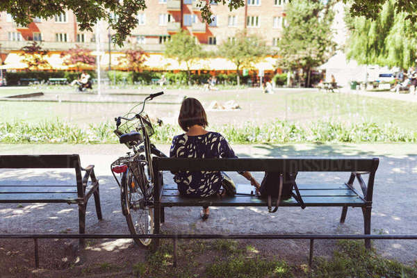 Rear view of businesswoman sitting on park bench by bicycle Royalty-free stock photo