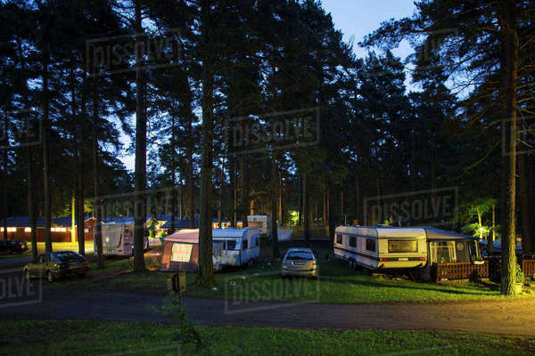 Caravans parked in travel trailer park amidst trees at dusk Royalty-free stock photo