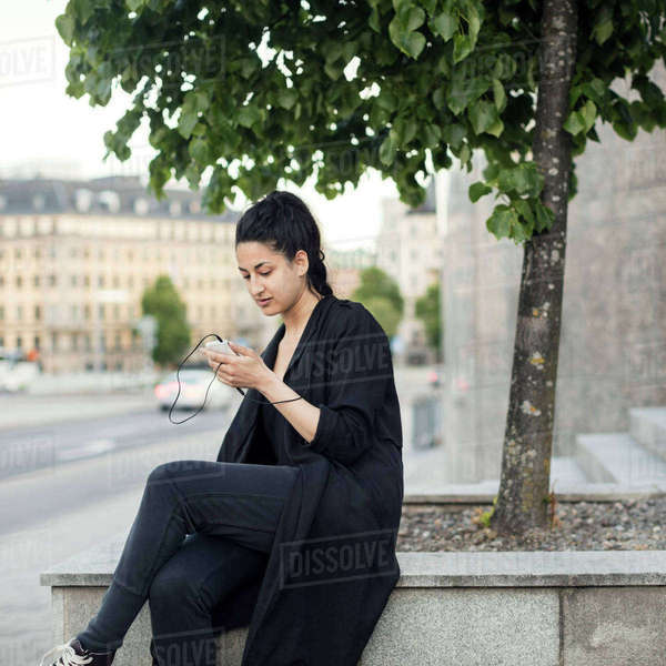 Young woman using smart phone while sitting on retaining wall in city Royalty-free stock photo