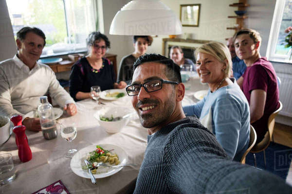 Portrait of smiling man taking selfie with family and friends at ...