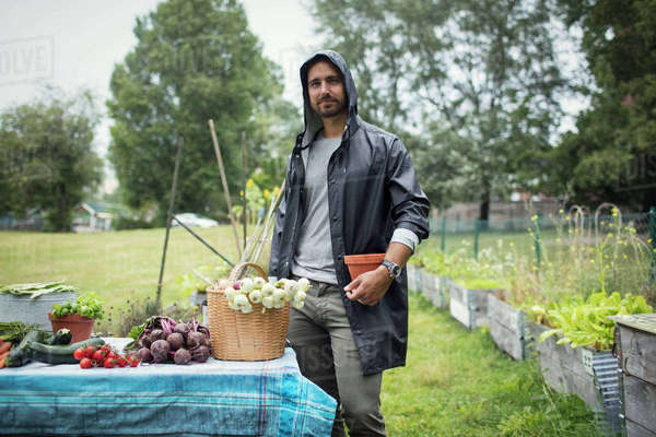 Portrait of mid adult man standing by freshly harvested vegetables on table at urban garden Royalty-free stock photo
