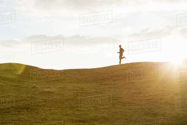 Distant view of man jogging on grassy hill against sky during sunny day Royalty-free stock photo