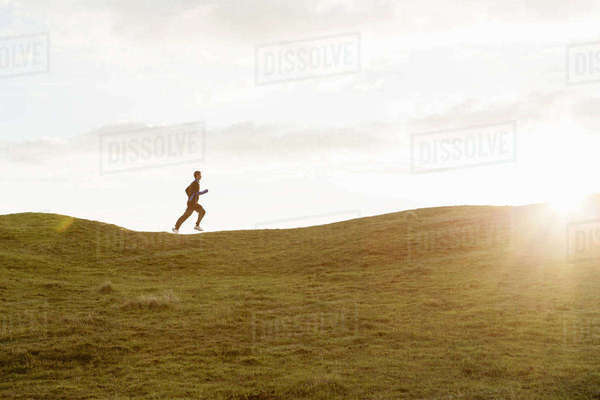 Distant view of man jogging on grassy hill against sky during summer Royalty-free stock photo
