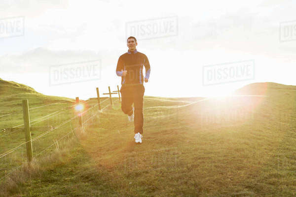 Mid adult man jogging on grassy field during sunny day Royalty-free stock photo