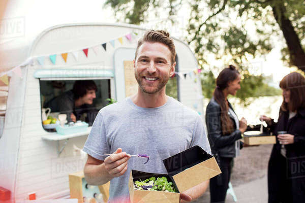 Smiling male customer holding disposable salad box against food truck with friends and owner in background Royalty-free stock photo