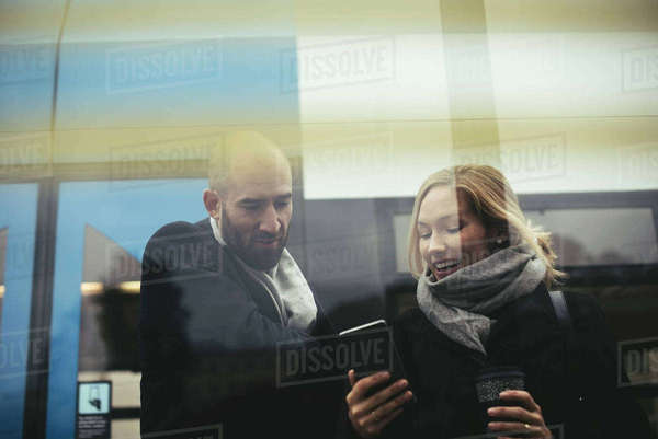 Business people using mobile phone while standing against tram Royalty-free stock photo