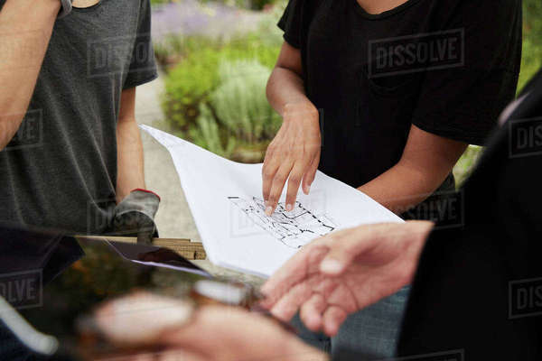 Midsection of female garden architect explaining blueprint to colleagues Royalty-free stock photo