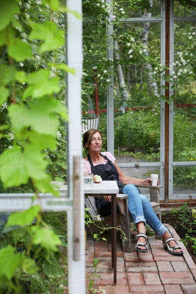 Female gardener resting in glass house Royalty-free stock photo