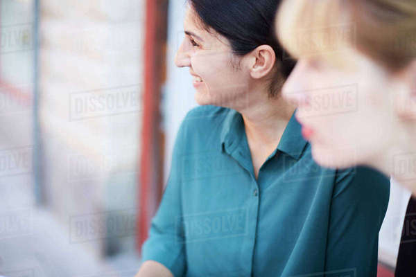 Smiling mid adult businesswoman with female colleague looking away outside office Royalty-free stock photo