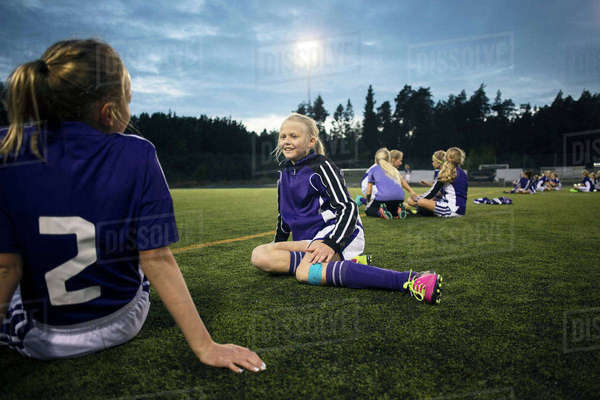 Girls relaxing on soccer field against sky Royalty-free stock photo