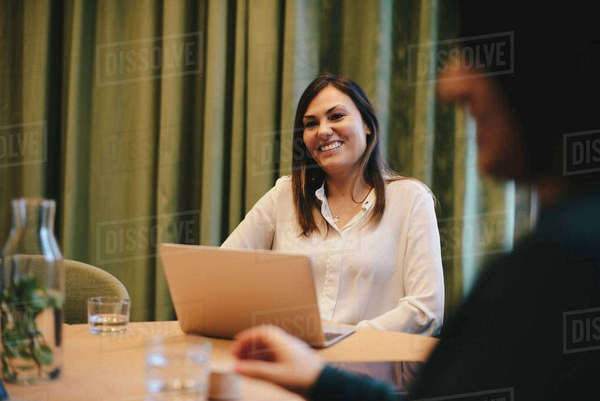 Happy businesswoman sitting wit laptop at conference table in board room Royalty-free stock photo