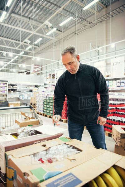Mature manager looking at cardboard boxes at supermarket Royalty-free stock photo