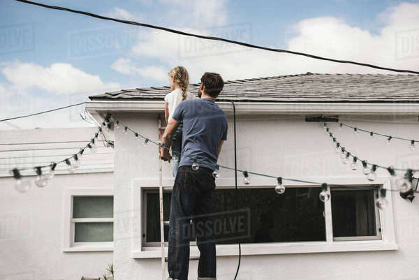 Rear view of man with daughter climbing up ladder at house Royalty-free stock photo