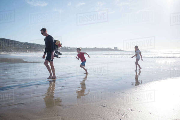 Full length of father with children enjoying vacation at beach on sunny day Royalty-free stock photo