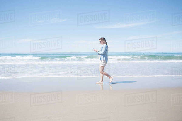 Full length side view of mature woman using mobile phone while walking at beach Royalty-free stock photo