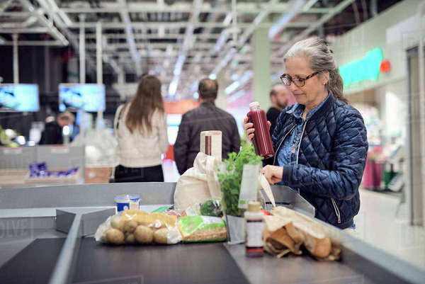Mature woman keeping juice bottle in bag while standing at checkout counter Royalty-free stock photo