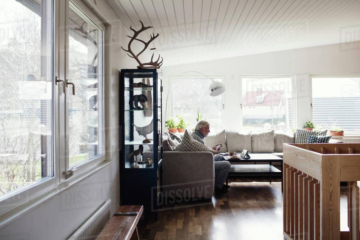 Full length of senior man sitting on sofa in living room at home ...