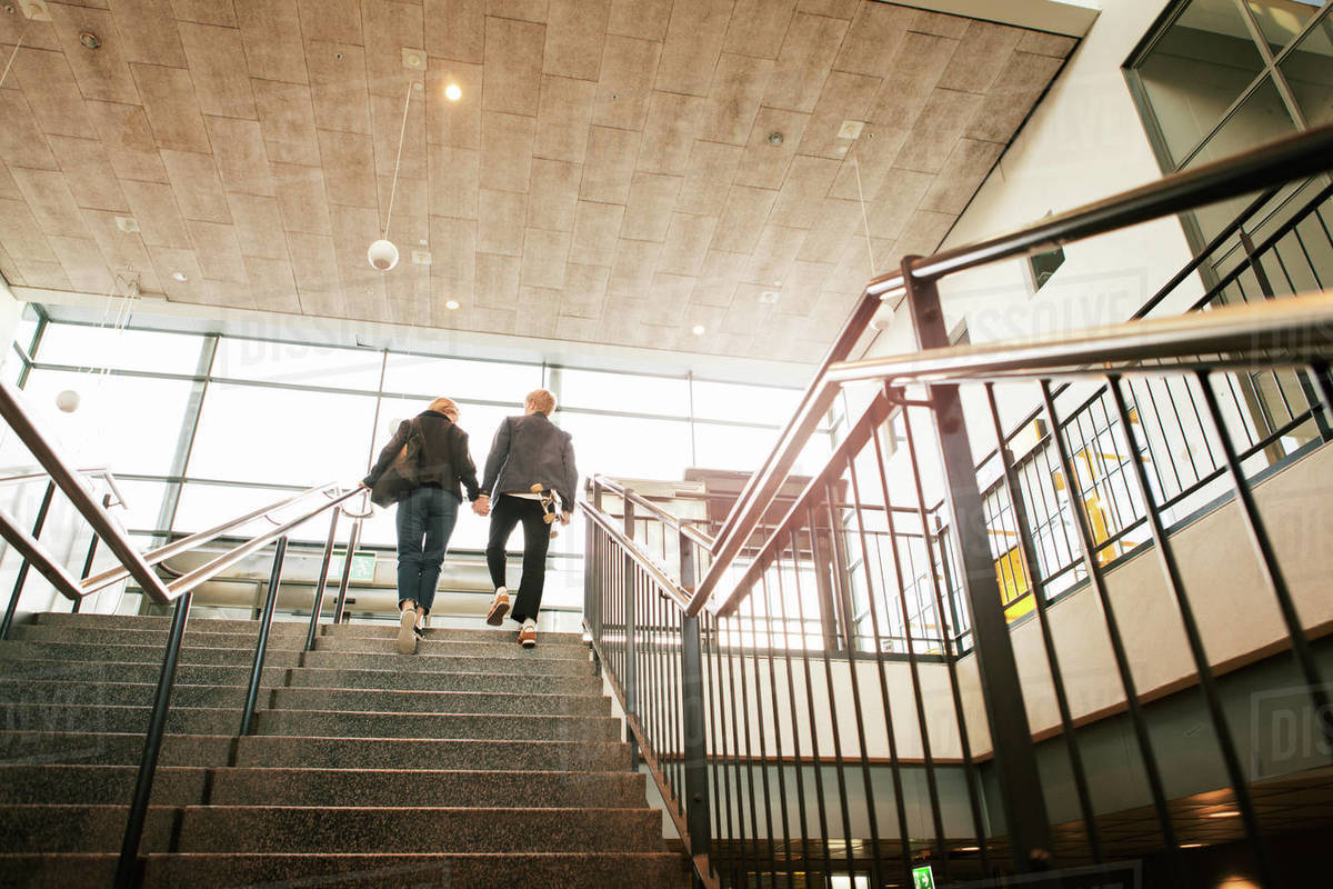 Low Angle View Of Young Couple Moving On Staircase At Subway Station